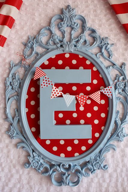 "center piece-using UNG Drill frame from ikea spray painted light blue with red and white polka dot background and then attached with hot glue a cardboard ""E"" also spray painted blue."