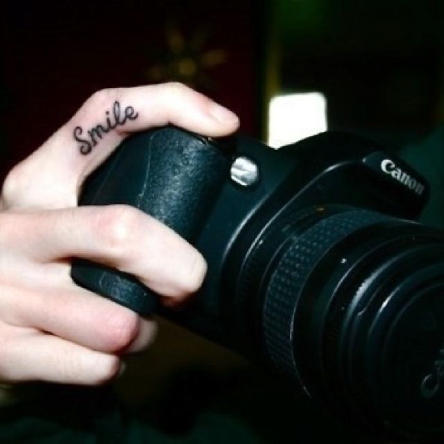 """tattoo on the finger you press the shutter button with that says """"smile"""". LOVE."""