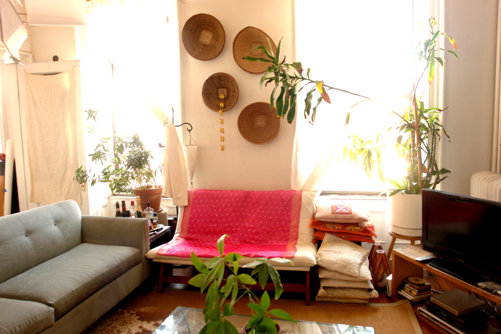 The green plants add a dreamy feel to the living room. Travel souvenirs on the wall and Indian fabric on the couch make the space very personal and cozy.