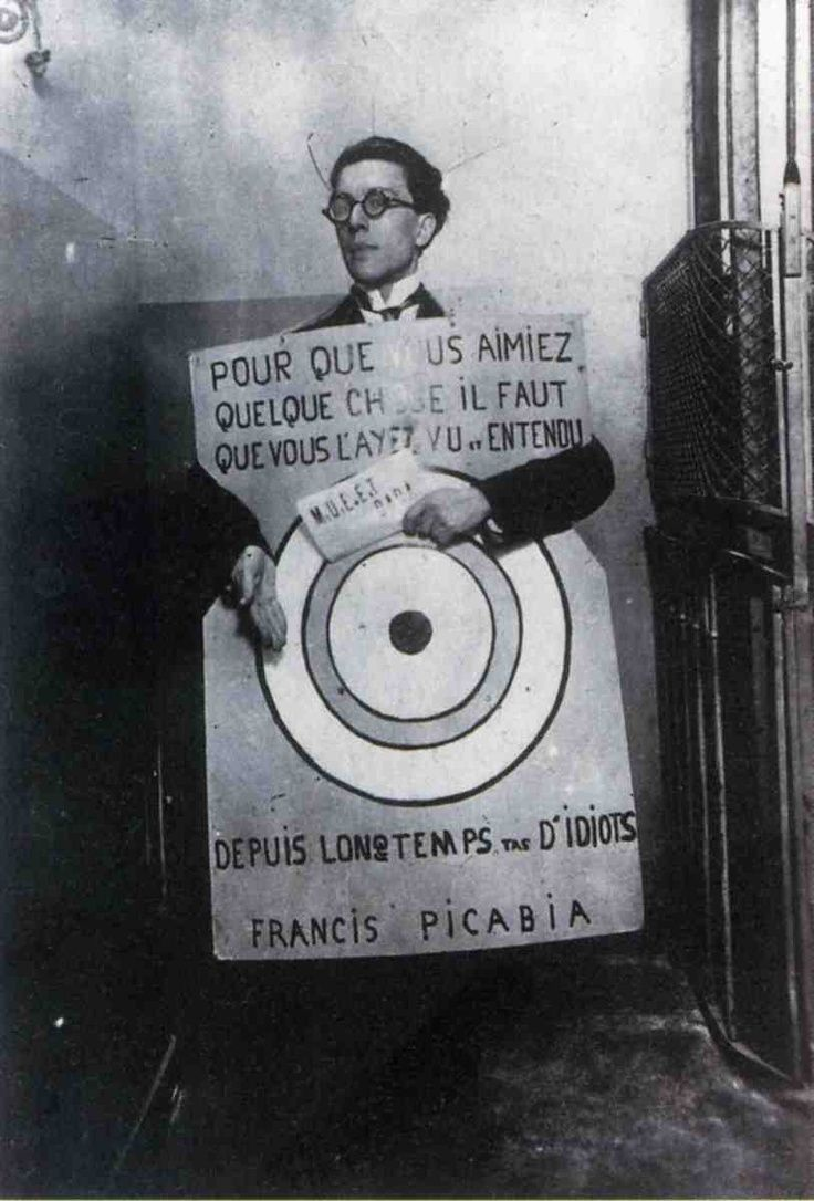"""André Breton at a Dada festival in Paris, March 27, 1920, wearing a slogan by Francis Picabia: """"In order to love something you need to have seen and heard it for a long time bunch of idiots."""""""