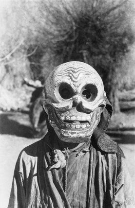 Lhasa mummer in skull mask, close-up, performing in the grounds of the British Mission residency in the Dekyi Lingka. This mask represents the Guardian of the Cemetery figure who appears frequently in Tibetan drama.