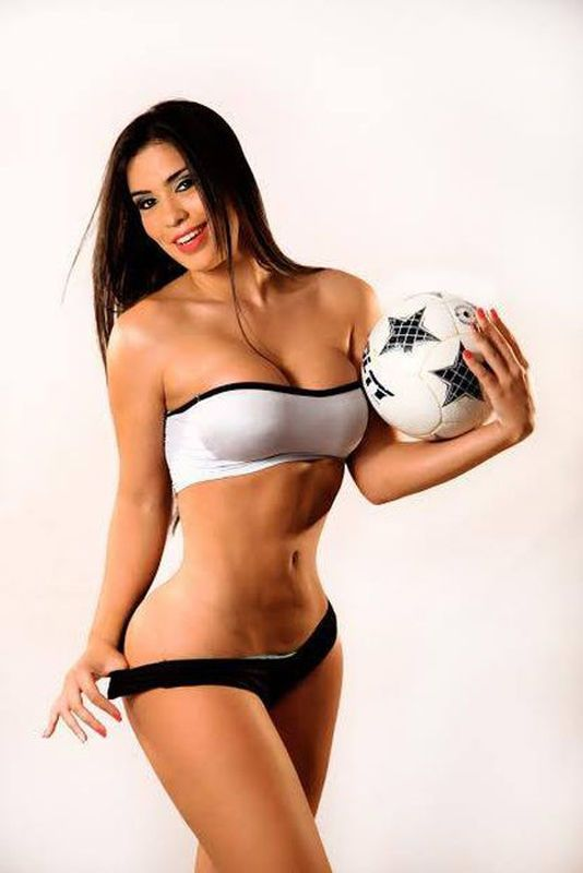 Sexy Girl Soccer Player With A Ball On A Green Background