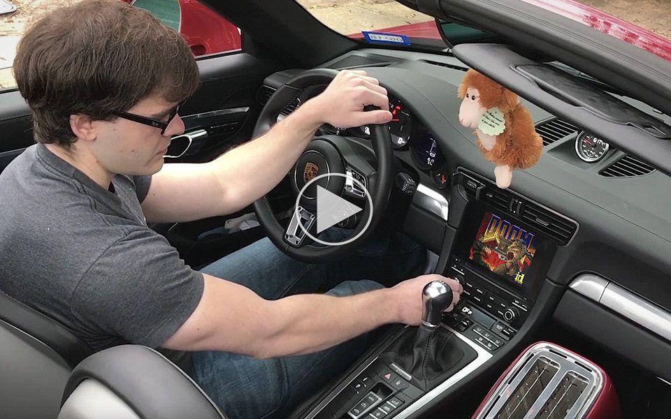 Fyr med overskud spiller Doom på skærmen i sin Porsche 911