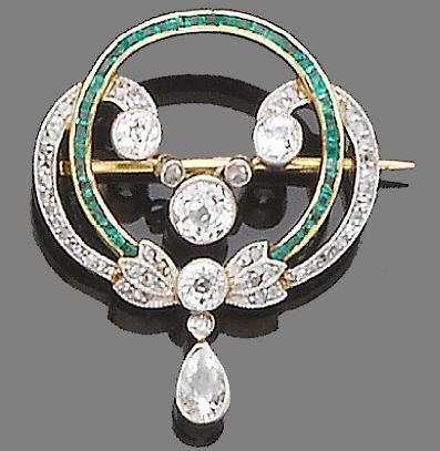 An emerald and diamond brooch, circa 1910 Designed as a millegrain-set old brilliant and rose-cut diamond swirl, surrounding a calibré-cut emerald circlet, suspending at its centre a millegrain-set old brilliant-cut diamond swag centre and at its base a collet-set pear-shaped diamond drop, mounted in silver and gold, diamonds approx. 1.80ct. total, length 3.3cm