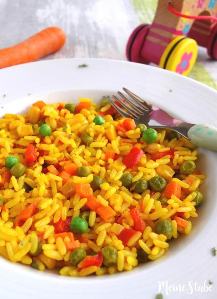 Kinder Paella mit buntem Gemüse, ein vegetarisches Reisgericht Kinder Paella vegetarisch, mit Erbsen, Mais und Tomaten
