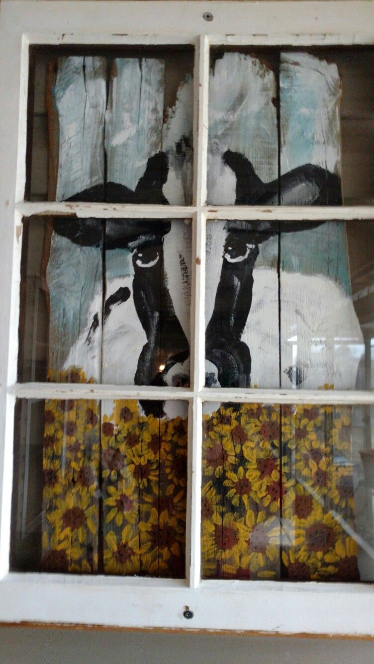 old window frame with hand painted cow looking in the window cow
