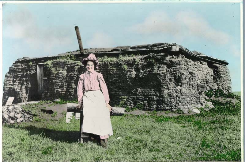 dress and bonnet smiling for the photographer in front of her sod house.