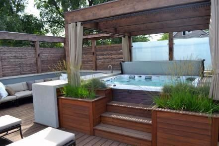 A serene urban getaway, this gorgeous rooftop deck features ipe decking, a built-in hot tub, cedar pergola, outdoor bar and a chic fire pit seating area. #buildingadeck