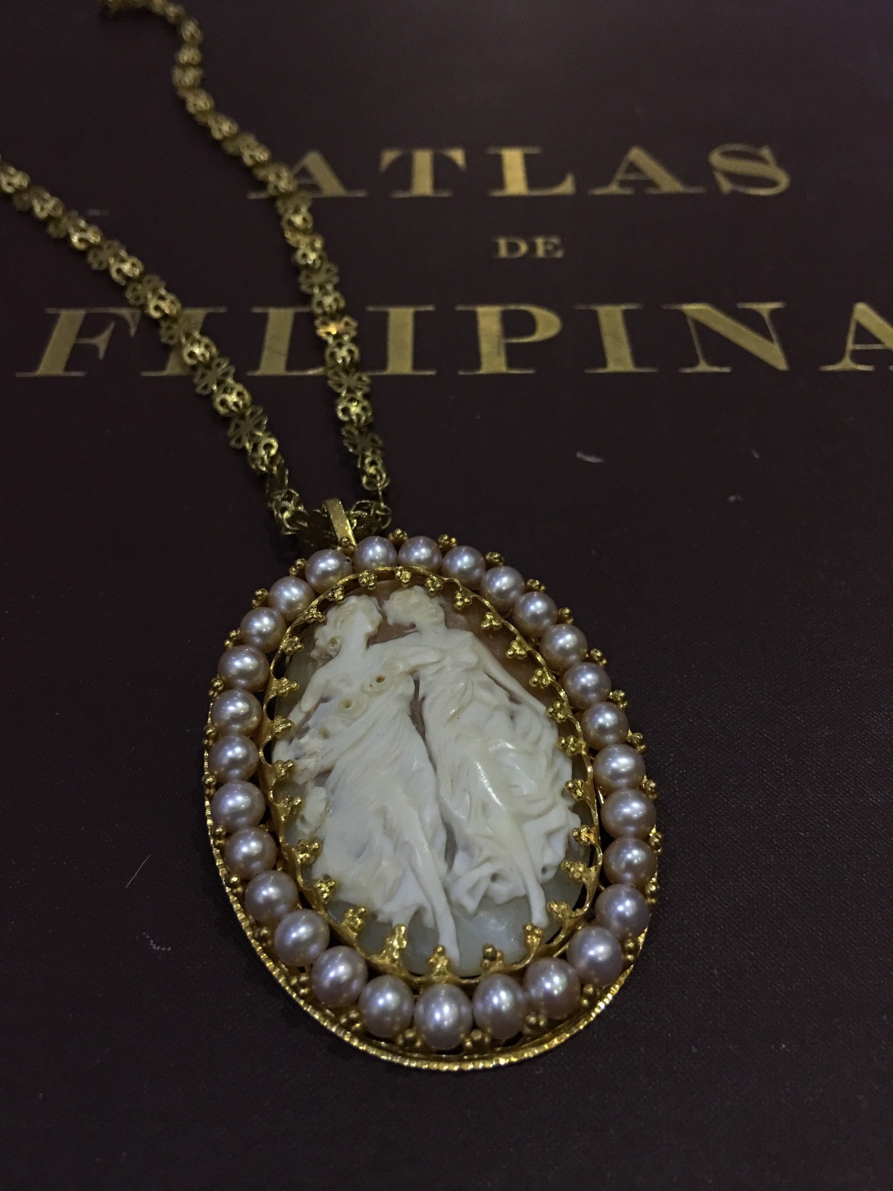 Handcarved shell Cameo Pendant of two sisters in 14K yellow gold and accentuated with white seed pearls