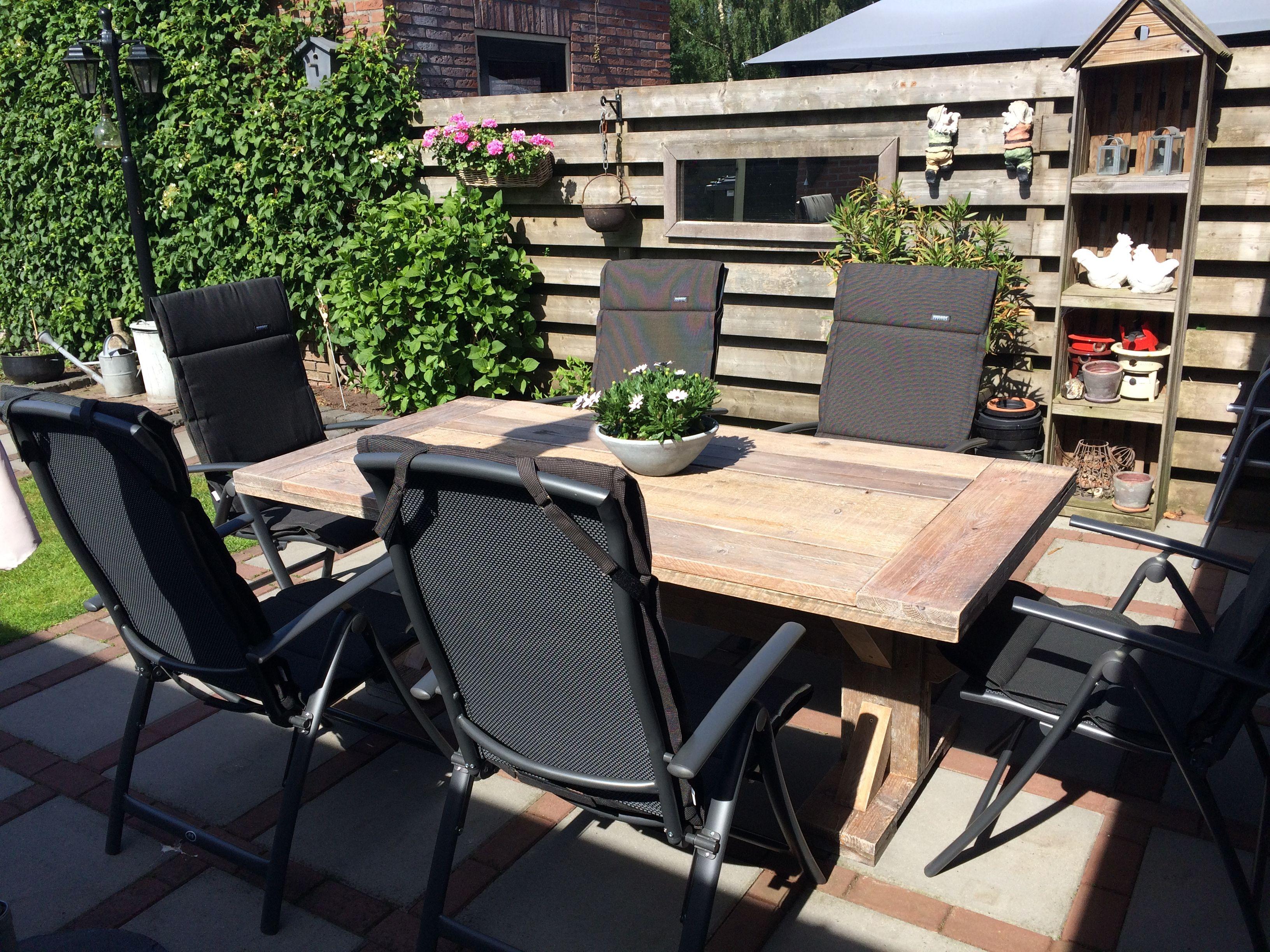 Houten tafel met zes zwarte tuinstoelen en zwarte for Zwarte tuinstoelen