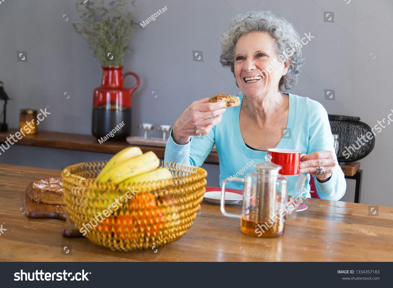 Happy senior lady enjoying dessert. Elderly woman sitting