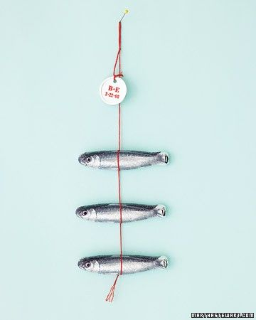 A whimsical wedding-day catch, this trio of chocolate fish is designed to be pinned up on a board at the reception. The foil-wrapped critters (from Chocolat Michel Cluizel Paris) are strung on embroidery floss; the label is a simple hang tag.