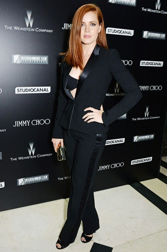 Amy Adams Wears A Black Bra Layered Under A Black Suit With Leather Detailing Peep Toe Pumps And A Metallic Clutch