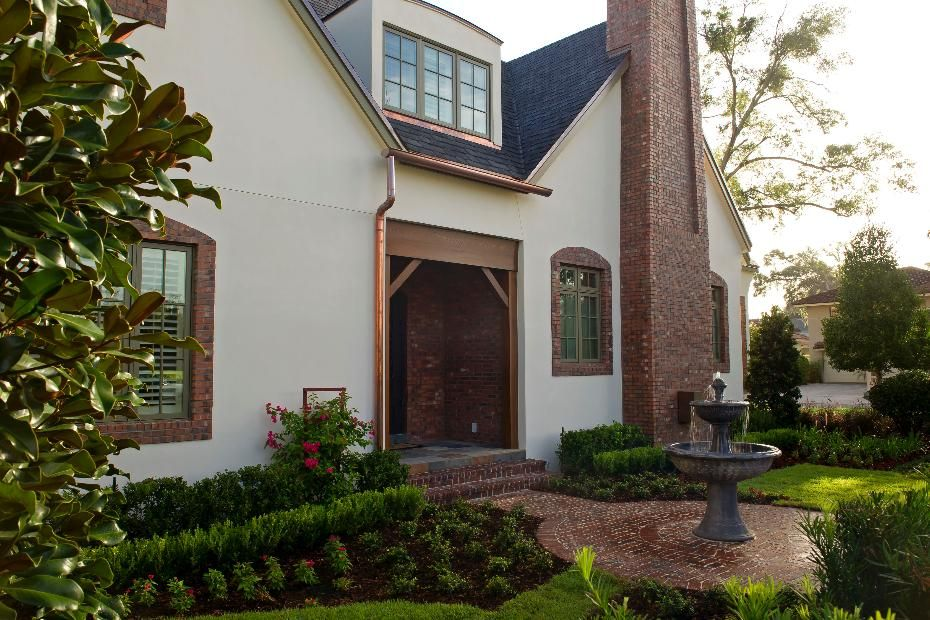 English Cottage style home with fountain and brick detailing