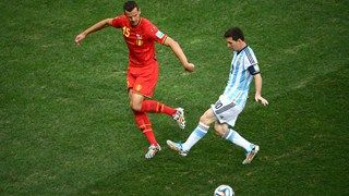 Lionel Messi of Argentina and Daniel Van Buyten of Belgium compete for the ball at World Cup 2014