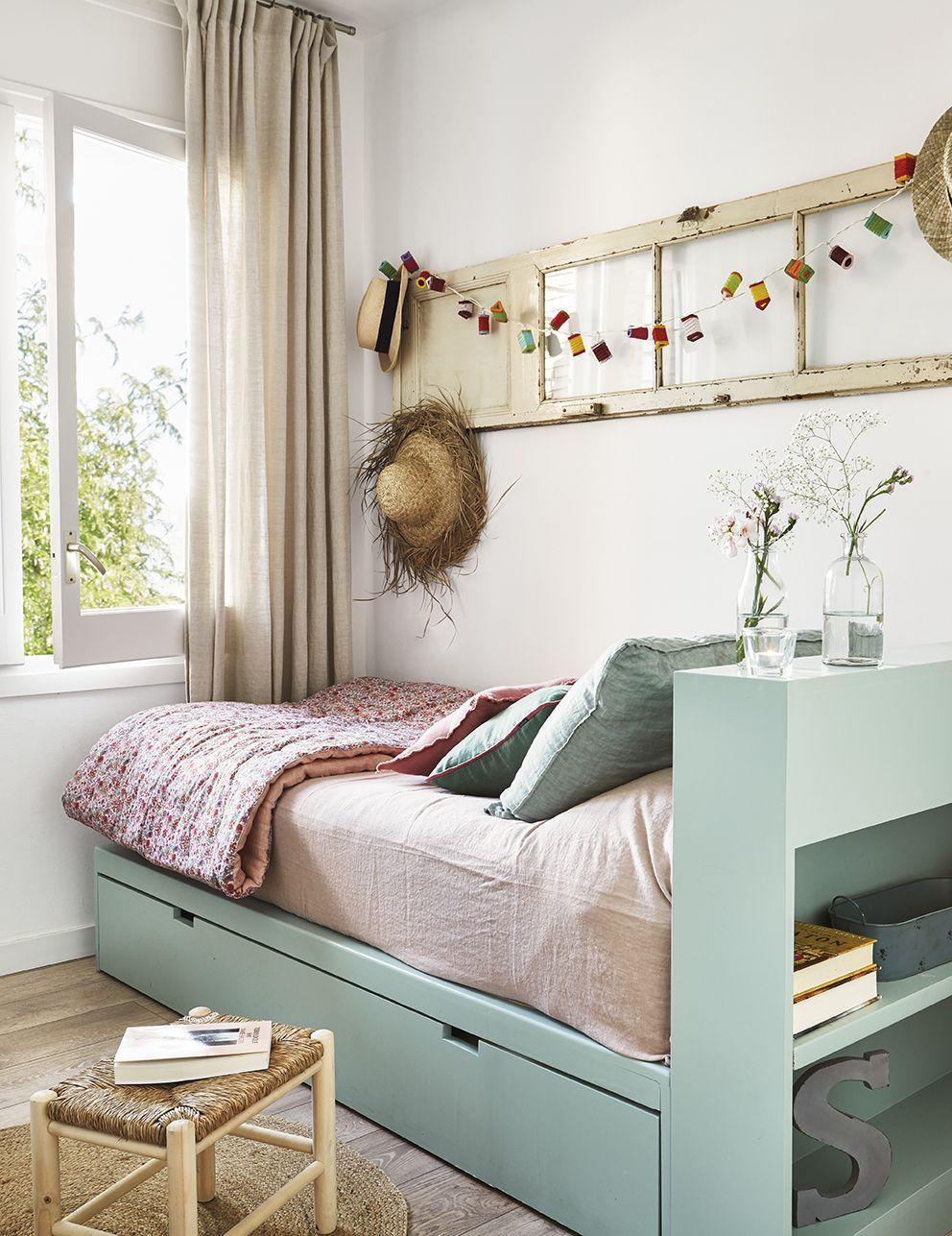 Pequeño dormitorio en tonos pastel claro y sombreros y guirnalda