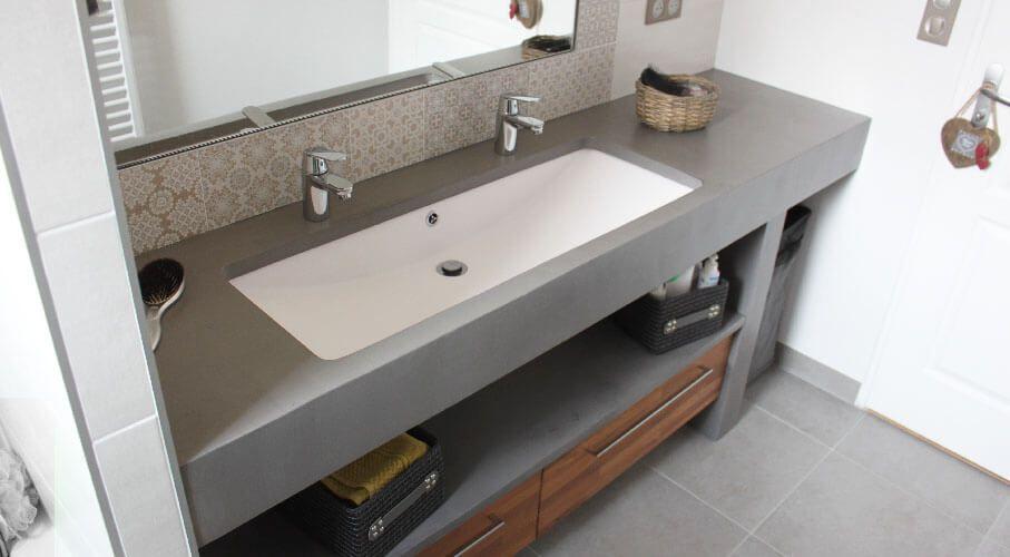 Un meuble en béton ciré avec une grande vasque et agrémenté ...