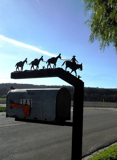 Mailbox with silhouette of cowboy and horse leading mule team. Central Coast, California