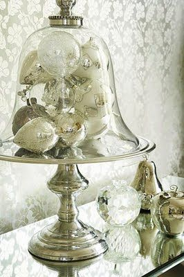 cloche filled with glass, silver, and mercury glass ornaments