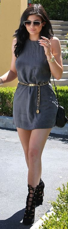 Who made Kylie Jenner's gold chain belt, gray dress, watch, sunglasses, cut out boots, and leather handbag?