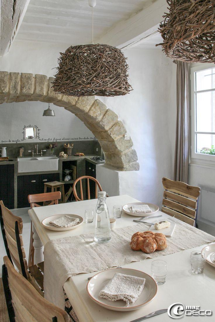 Salle à manger et cuisine séparées par un arc en pierre, assiettes