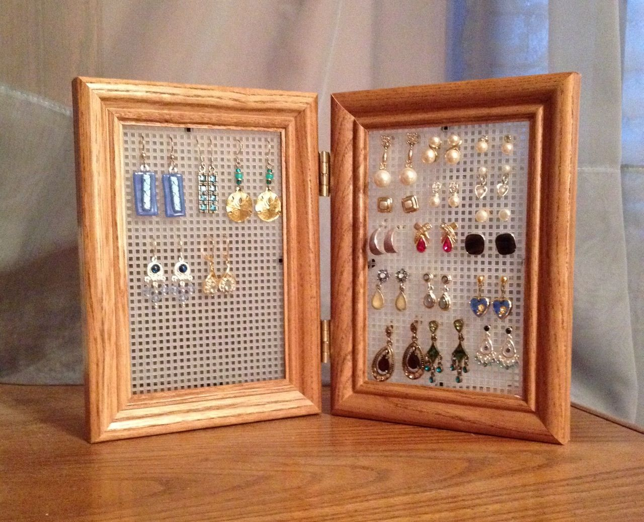 Easy DIY earring storage.  Remove the glass and backing from a hinged frame and replace with plastic canvas.  Can sit open on your dresser, or folds closed for storage or travel.  I have a separate set I use for all my holiday earrings that I don't want sitting out all year long.