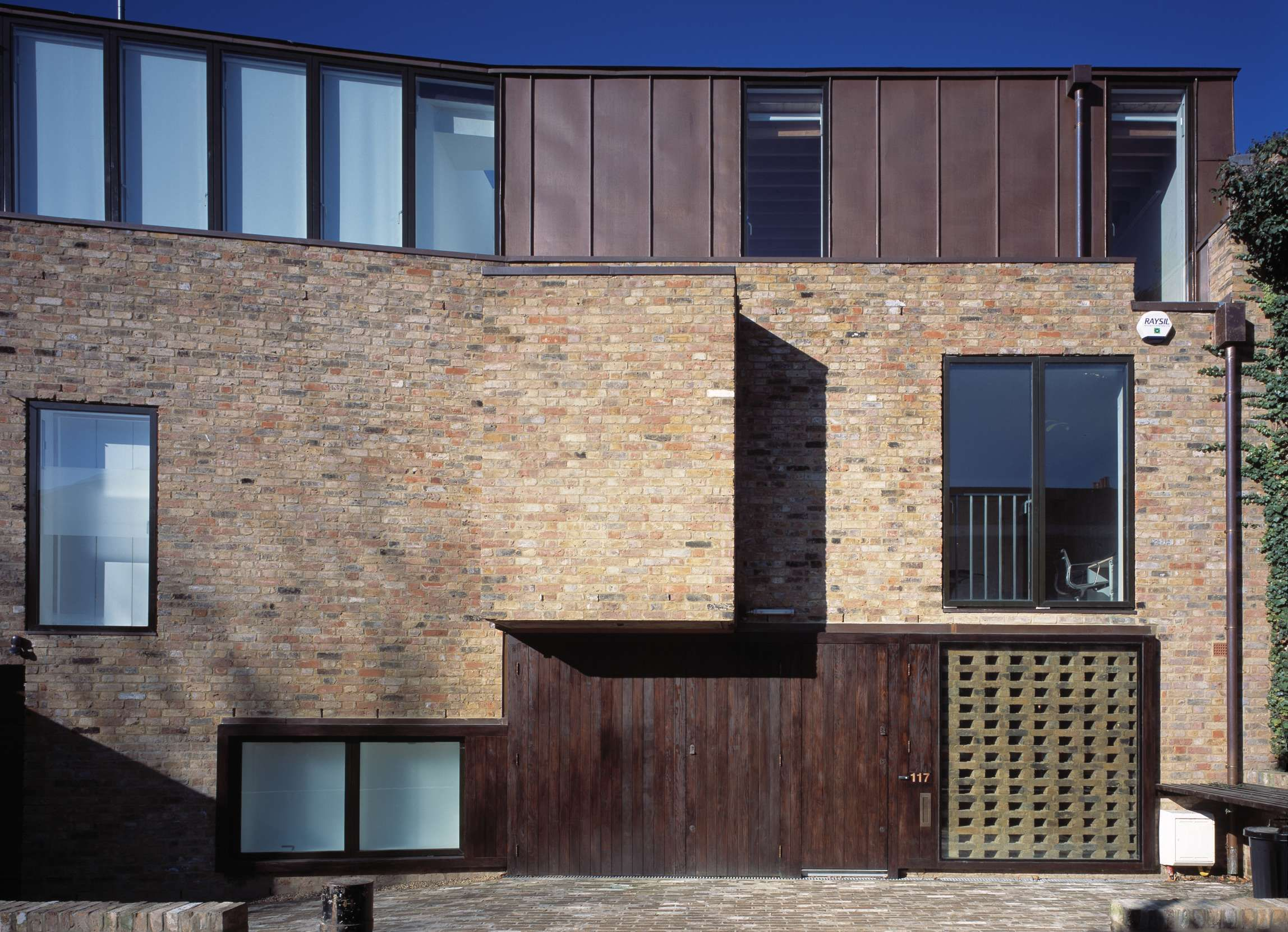 Interesting facade using brick and metal cladding by for Brick and stone house facades