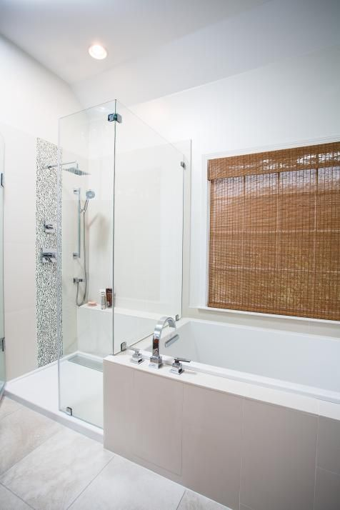 A large shower features a built-in bench seat, glass shower doors