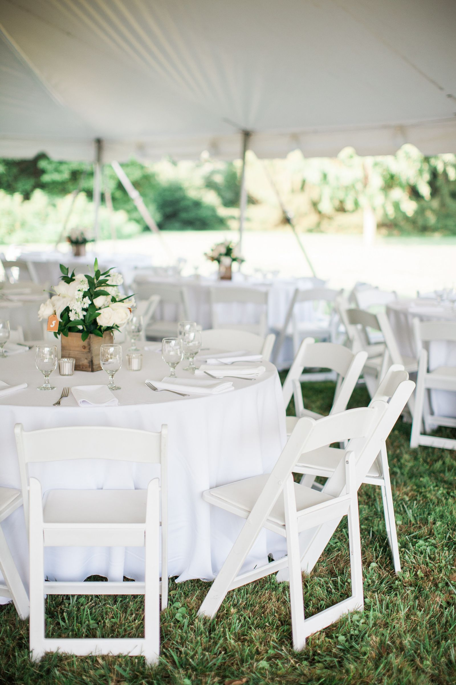 round tables and white wooden chairs at cylburn arboretum tent