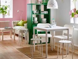 Zona pranzo con tavolo due sedie e due sgabelli bianchi e uno