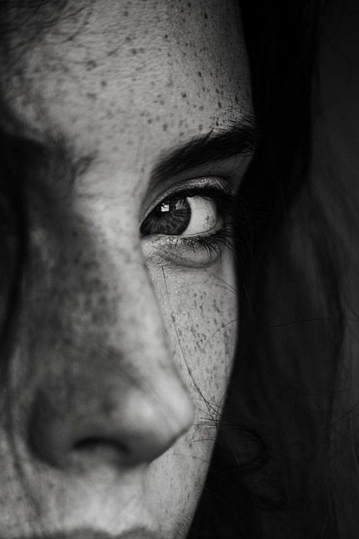 image noir et blanc, portrait noir et blanc, femme rousse avec des taches de rousseur, un œil caché, regard qui doute et scrute son interlocuteur