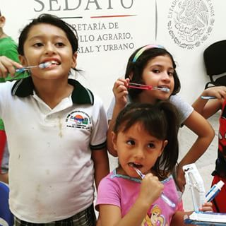 Children at the Ludoteca practise cleaning their teeth. # ...