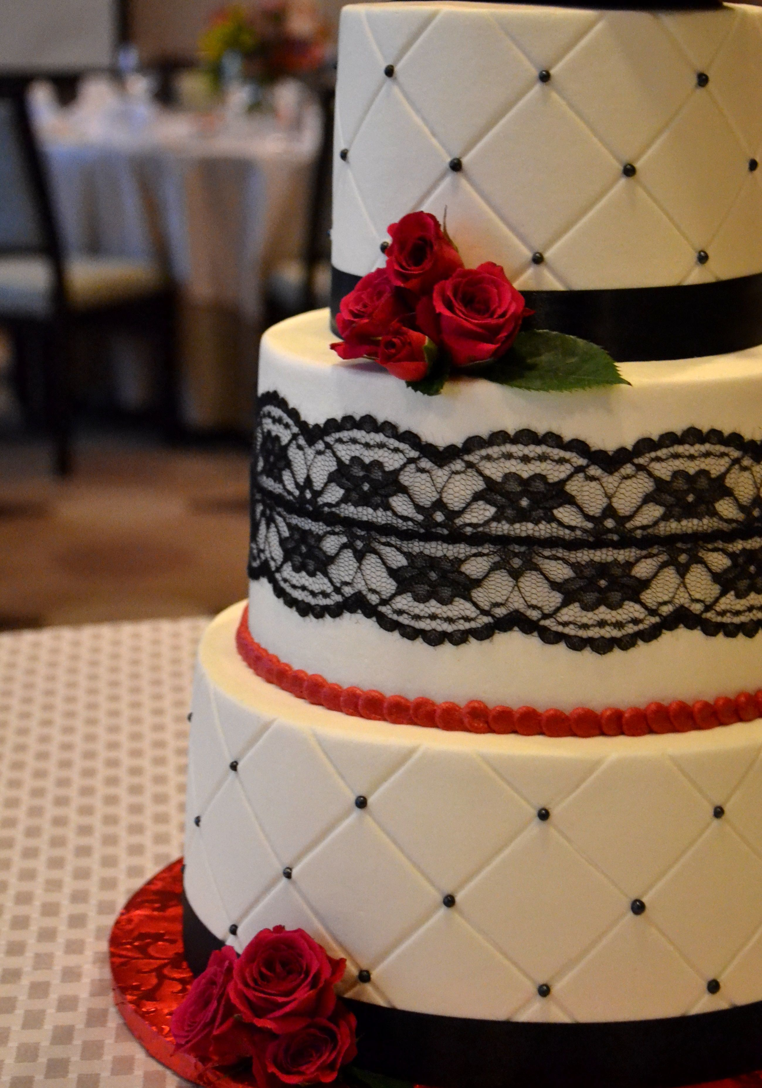 A Quilted Buttercream Wedding Cake With Black Lace And Pearl Details Fresh Red Flower Accent