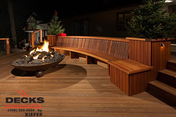 Large award winning deck with built in seating lighting for Fireplace on raised deck