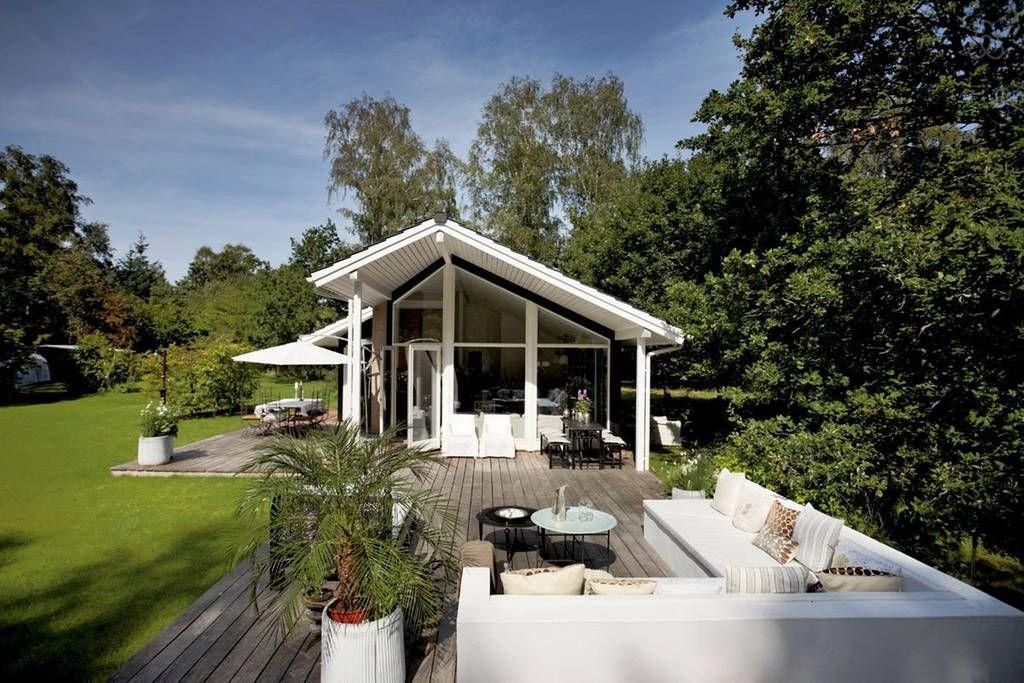 Høj himmel og solskin på terrassen i familien Nordal Clausens sommerhus. Da familien overtog det 70 m² store sommerhus, gik de først i gang med at få udbygget den eksisterende terrasse til dobbelt størrelse. Det har givet plads til flere typer af uderum o