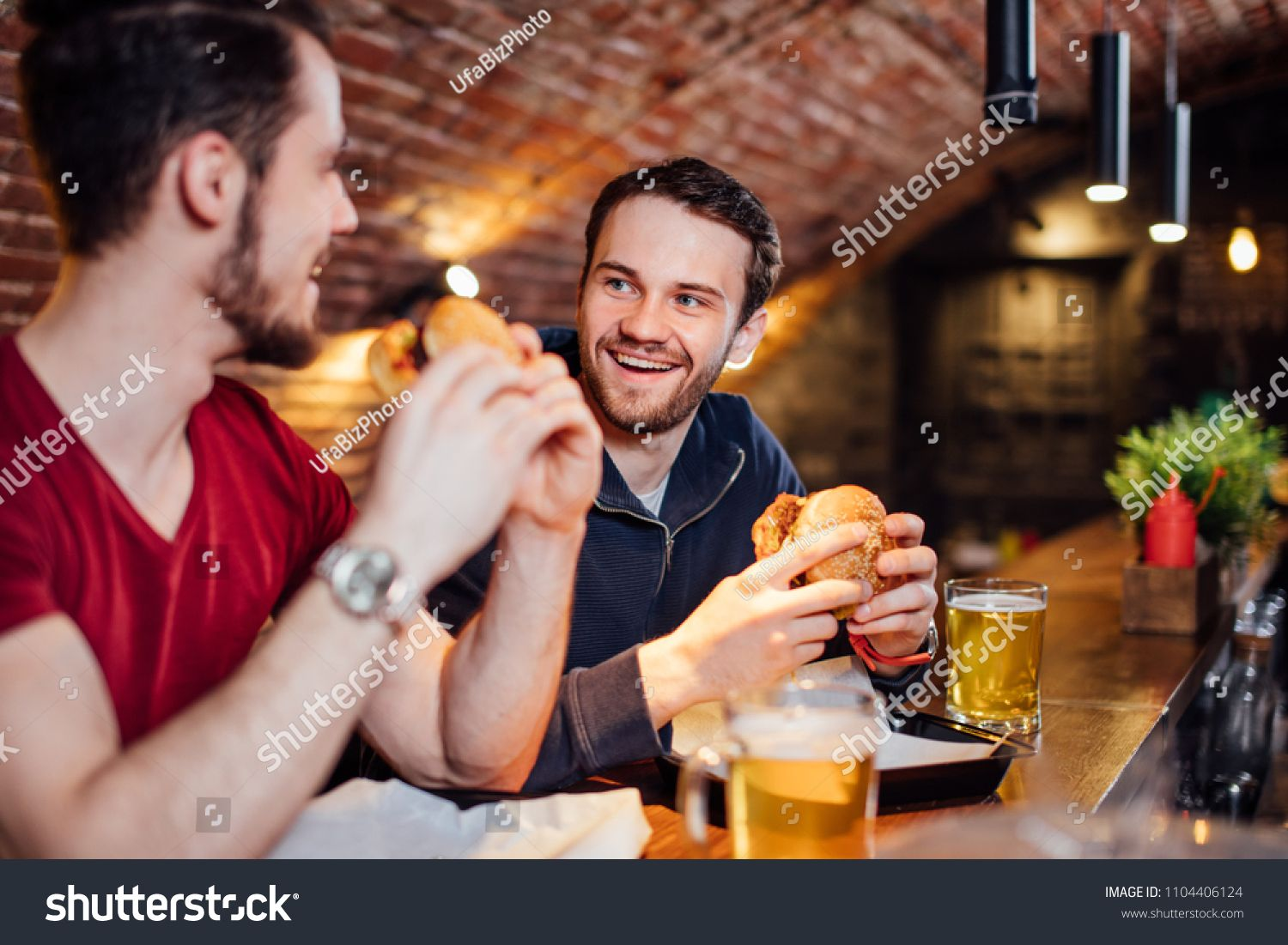 Two Happy Male Friends Having Dinner At Popular Burger Bar Young People Sitting Talking And Eating Burgers Drinking Beer Drinking Beer People Sitting People
