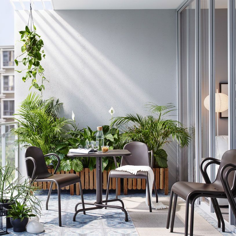 Liten balkong møblert med mørkebrunt sammenleggbart bord, fire stoler som kan stables og blomsterkasser i massiv akasie med grønne planter.