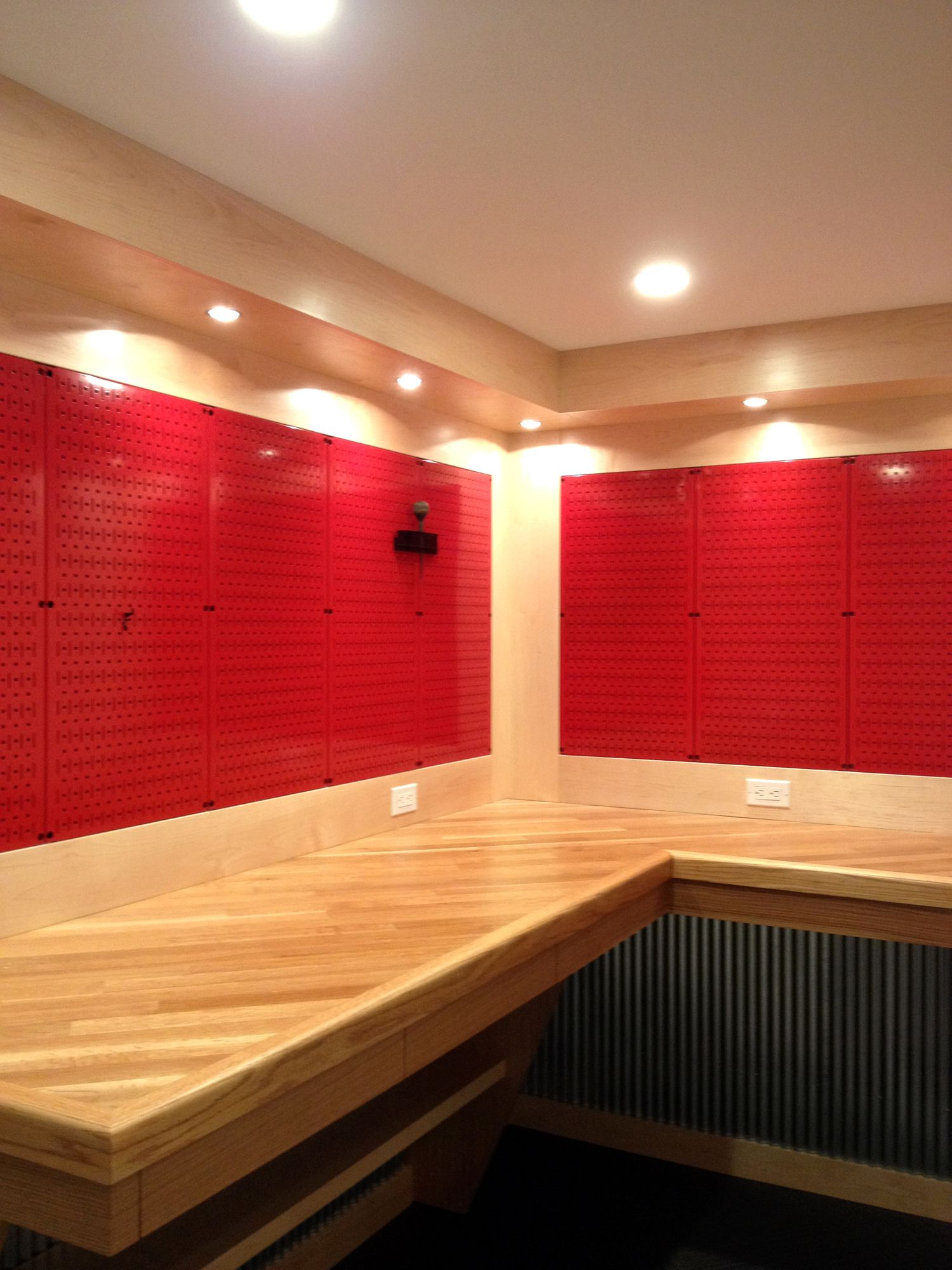A Really Nice Workbench With Red Metal Pegboard Panels From Wall