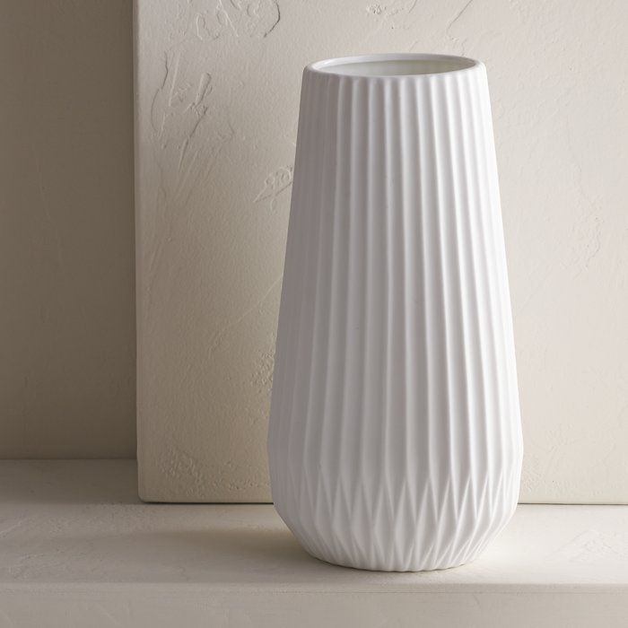 White Textured Table Vase is part of White Home Accessories Texture - Vases are a versatile decorative accent  Not only do they fill in the gaps on empty dining tables, end tables, and book shelves  They can hold other decorative accents, like fresh or faux flowers, sticks, and  more, and can brighten up a room  Take this vase for example a tapered cylinder shape with an allover geometric texture, it is crafted from stoneware  This piece measures 11 42'' H x 5 51'' W x 5 51'' D