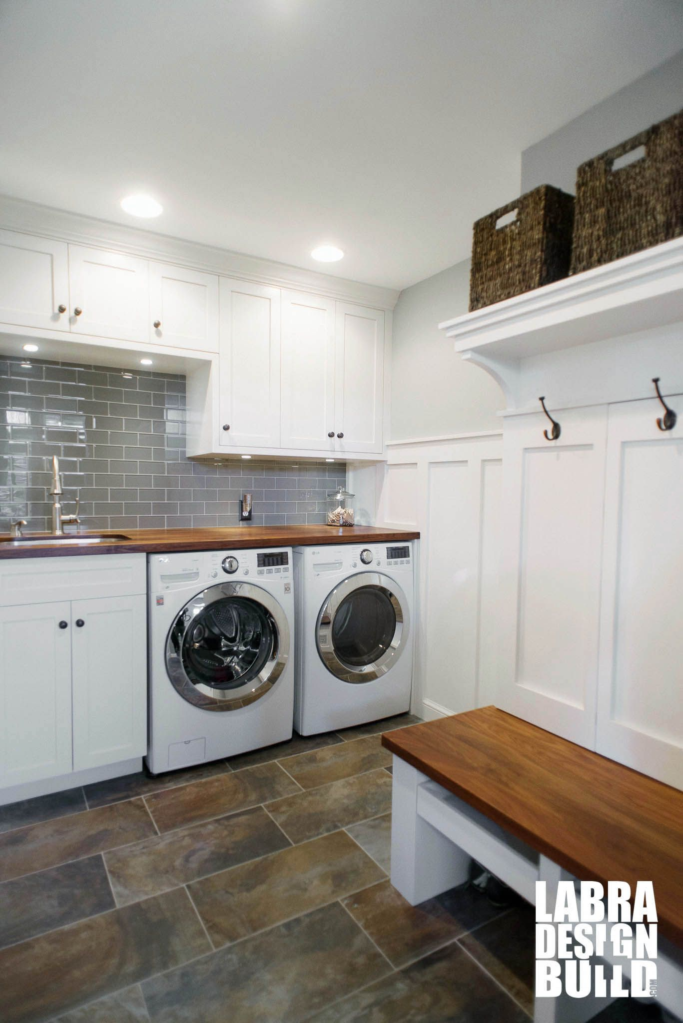 Custom Mudroom And Laundry Room Combo With White Cabinetry Wainscoting Slate Floors Walnut Wood Countertops Bench