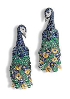 This beautiful piece of white gold jewelry is studded with emeralds, blue sapphires, white and yellow diamonds.