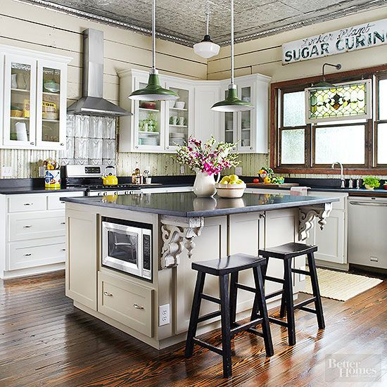 This beautiful kitchen melds reclaimed building materials, architectural elements, and vintage graphics in innovative ways. Tin details spark interest on the ceiling and above the range. Chip-painted boards create an inexpensive, high-impact backsplash, while corbels support the island's breakfast bar. Symbols of a different time -- including a sugar-curing sign, stained-glass window, and assorted advertising tins -- supply era-apt colors and motifs.