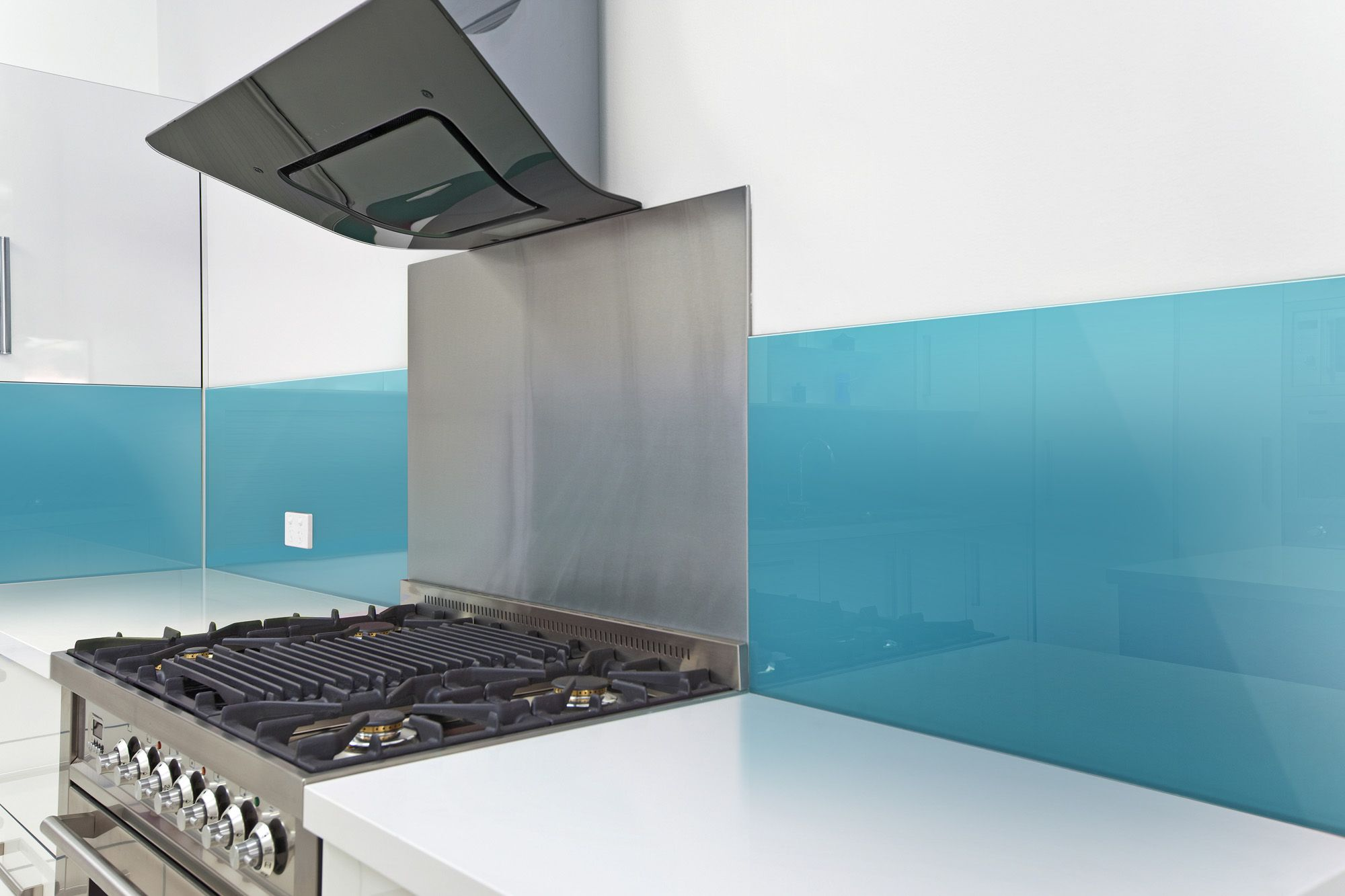 fun kitchen backsplash combining stainless steel behind the cooktop and high gloss wall panels around the