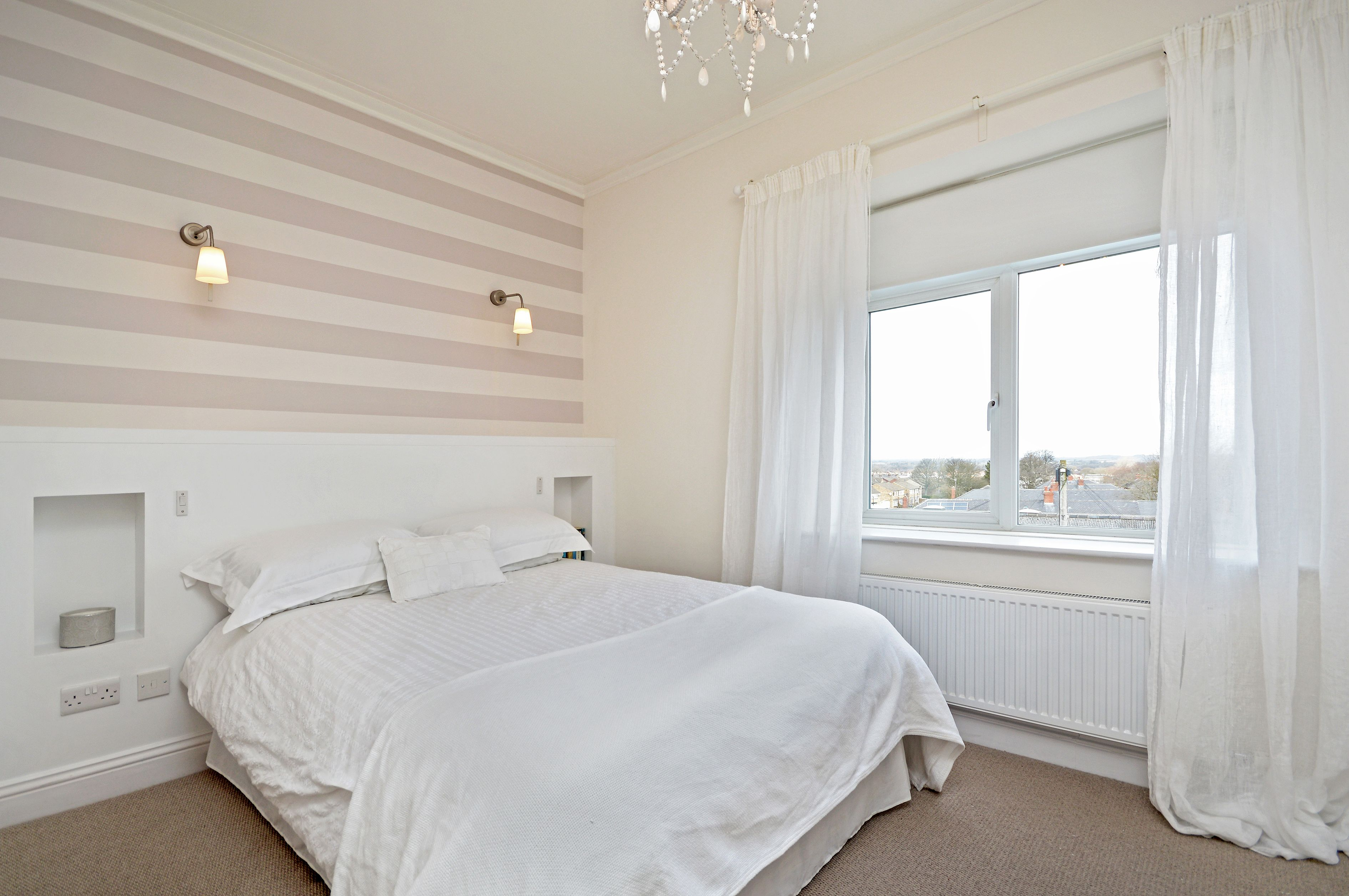 Bedroom With Grey And White Striped Wallpaper And Linen Curtains