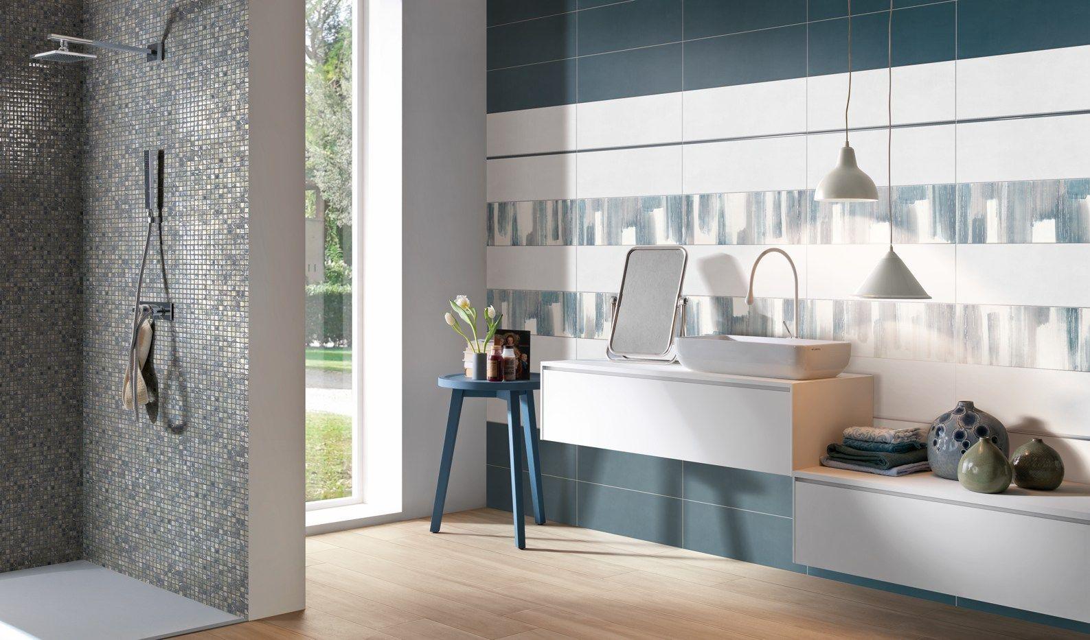 Un bellissimo bagno moderno con un rivestimento arricchito da inserti sui toni dellazzurro A