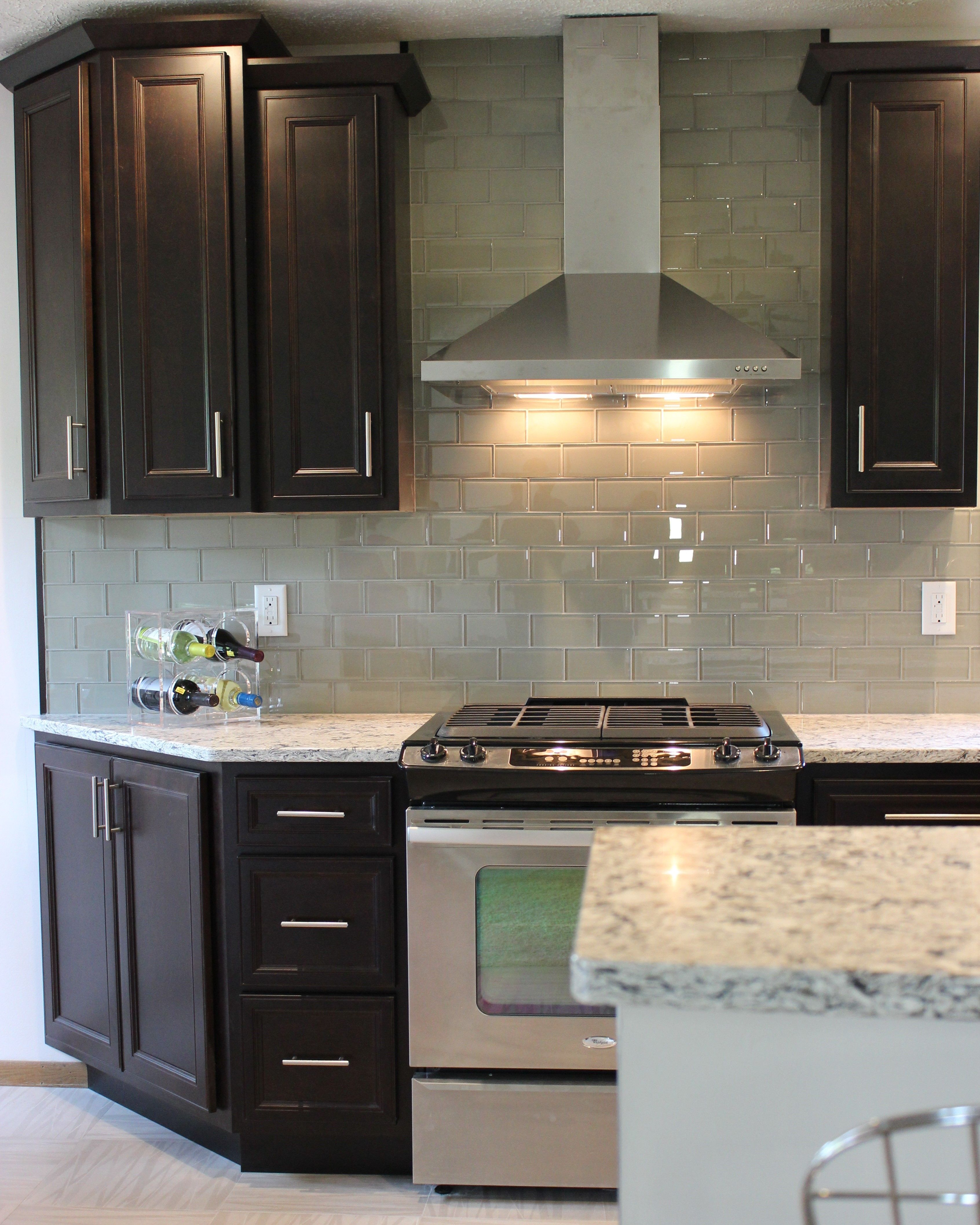 A Stainless Steel Chimney Style Hood Surrounded By Glass Tile And Dark Java Cabinetry Villagehomestor Kitchen Remodel Kitchen Dark Kitchen Cabinets
