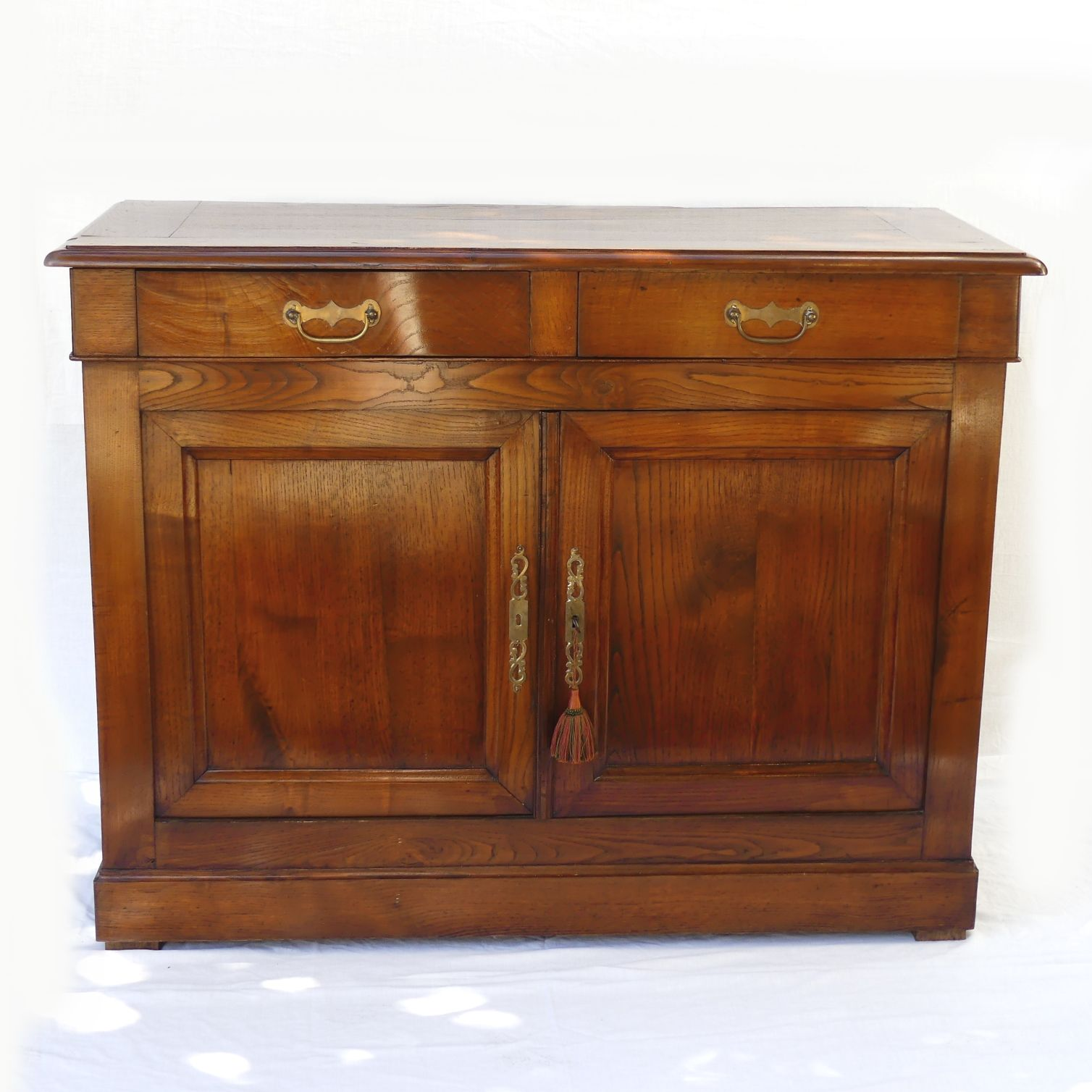 An Oak Sefton Powrie Cabinet Two Half Drawers The Panelled Doors With Decorative Br Key