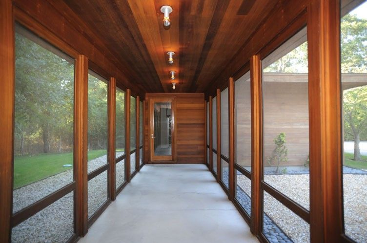I really want a glassed-in walkway connecting the main house to my husband's workshop and garage areas of our future dream home.  This is a not really the overall style of the walkway I would want, but it gives the general idea.  Source: Hamptons Real Estate
