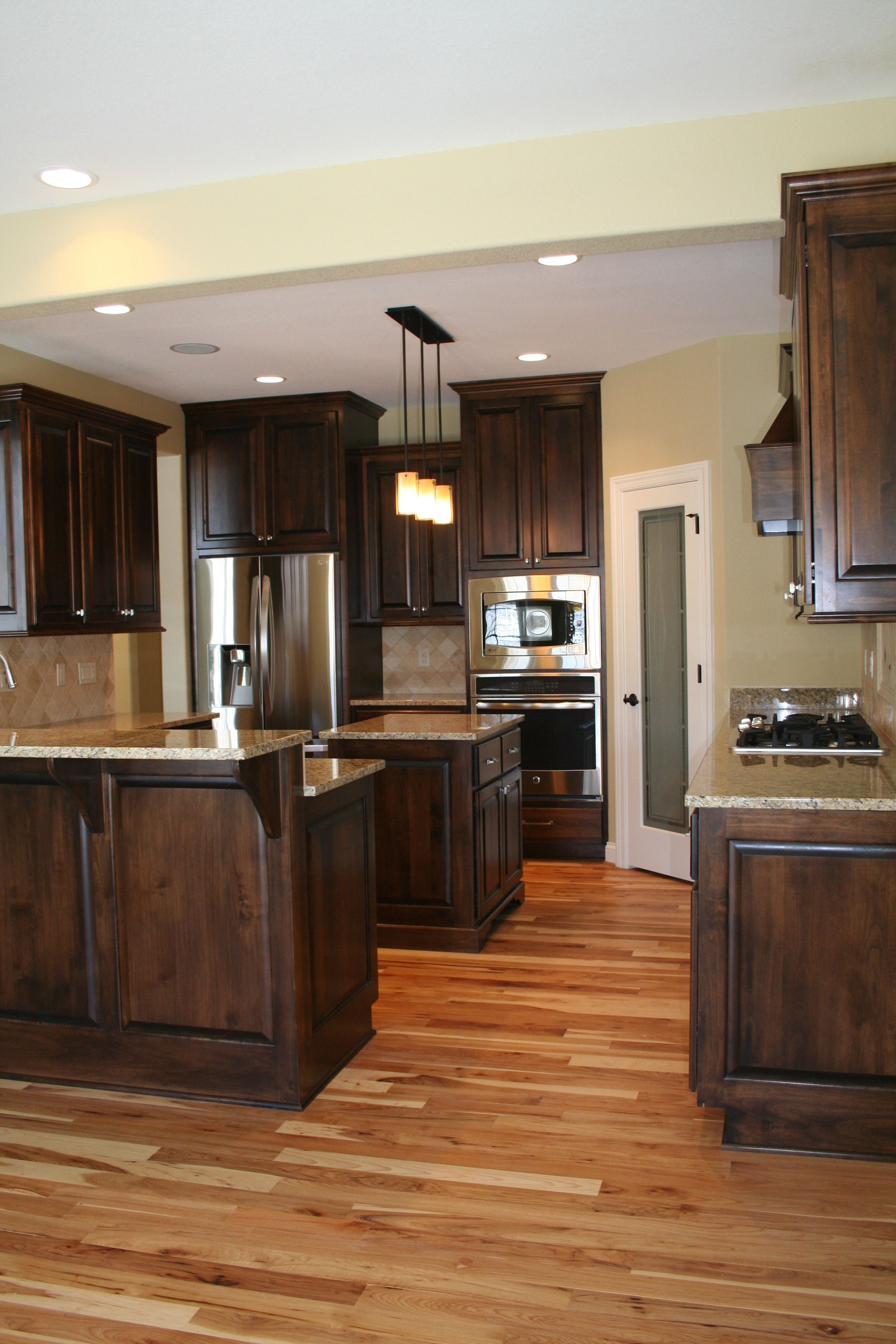 Alder Wood Cabinets Stainless Steel Appliances And Natural Hickory Hard Wood Flooring For More In Wood Floor Kitchen Hickory Kitchen Cabinets Hickory Kitchen