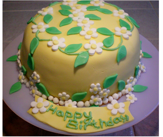 Summer home made birthday cake in yellow with green cake decorPNG